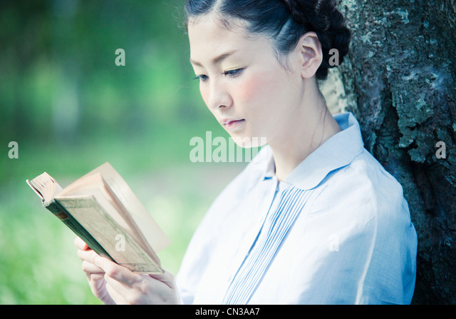 Young woman reading book, close up - Stock Image