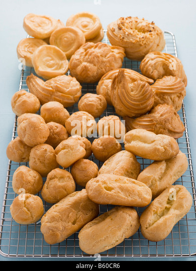 Selection of Choux Pastry Buns on a Cooling Rack - Stock Image