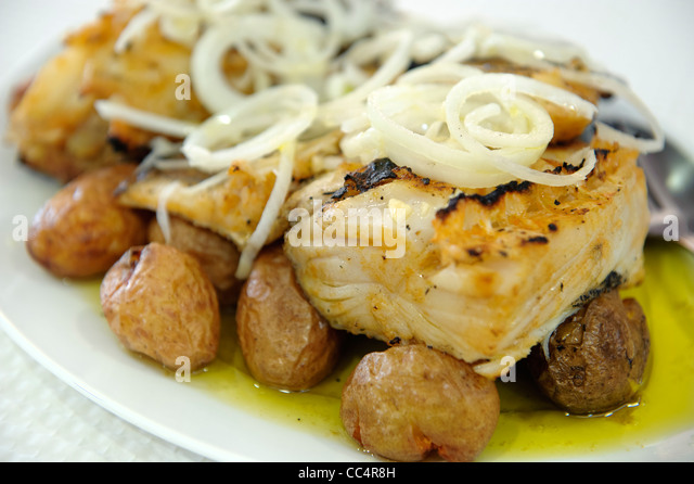 Typical portuguese dish Bacalhau a Lagareiro (cod fish with olive oil, onions and potatoes) - Stock Image