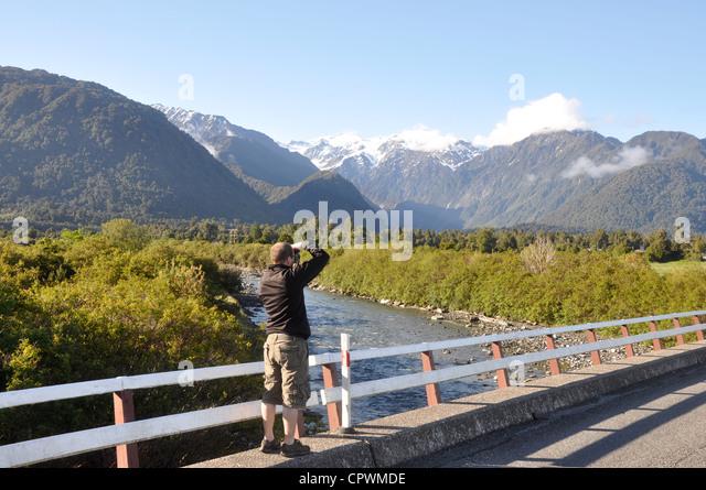 Tourist taking photo of mountains near Franz Josef, South Island, West Coast, New Zealand - Stock Image