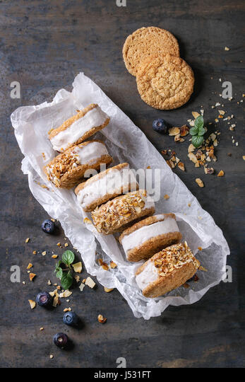 Set of homemade ice cream sandwiches in oat cookies with almond sugar crumbs, blueberries and mint on baking paper - Stock Image