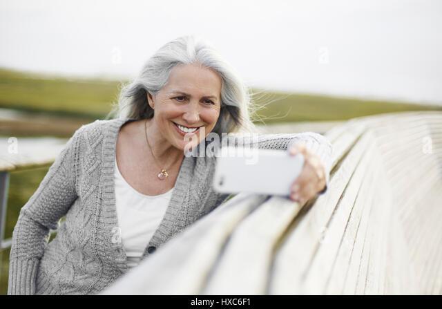Smiling senior woman taking selfie at boardwalk ledge - Stock Image