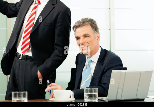 Senior Manager or boss in meeting contemplating new strategy - Stock Image