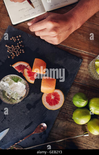 Top view of ingredients for making a cocktail with bartender taking notes. Cut grapefruit and black peppercorn with - Stock Image