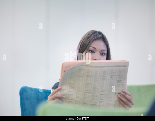 Businesswoman reading British newspaper - Stock Image
