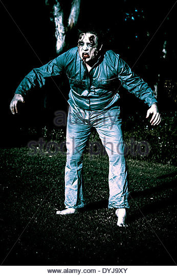 Creepy blue portrait of an evil dead horror zombie walking through graveyard during morning moonlight - Stock Image