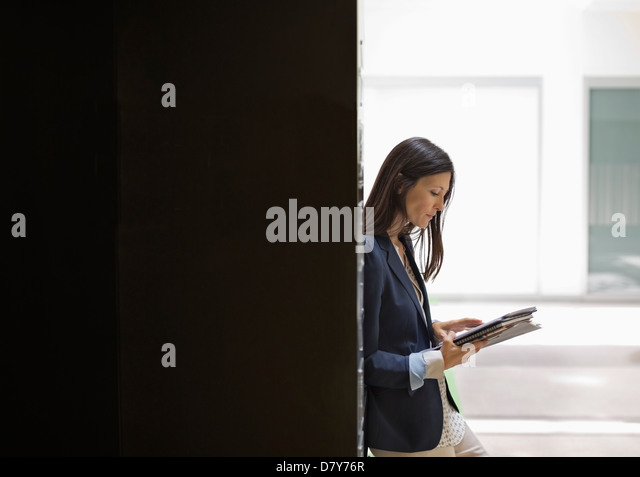 Businesswoman reading in office - Stock Image