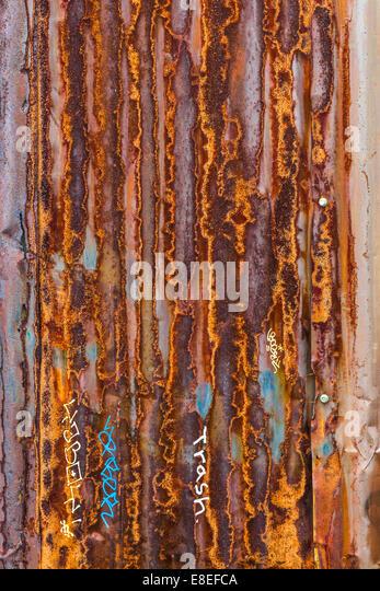 Corroded corrugated metal siding with minor graffiti - Stock Image