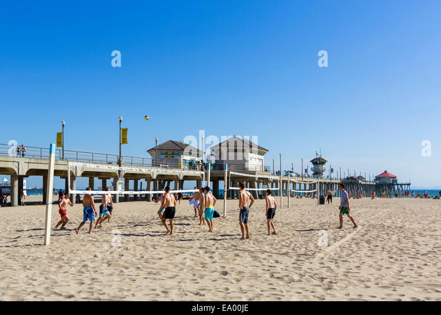 Young men playing beach volleyball in front of the pier in downtown Huntington Beach, Orange County, California, - Stock Image