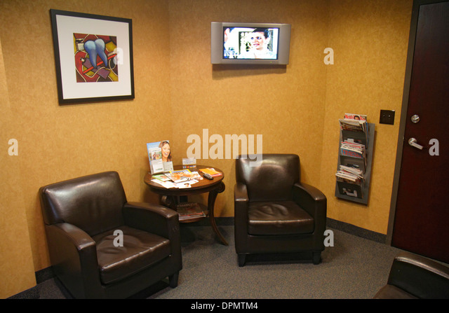 Miami Beach Florida dentist's office waiting room area furniture chairs flat panel TV television - Stock Image