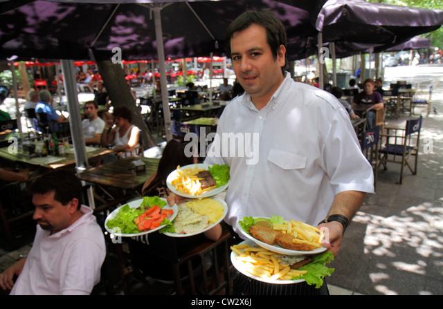 Mendoza Argentina Paseo Sarmiento pedestrian mall dining sidewalk cafe alfresco Hispanic man waiter job serving - Stock Image
