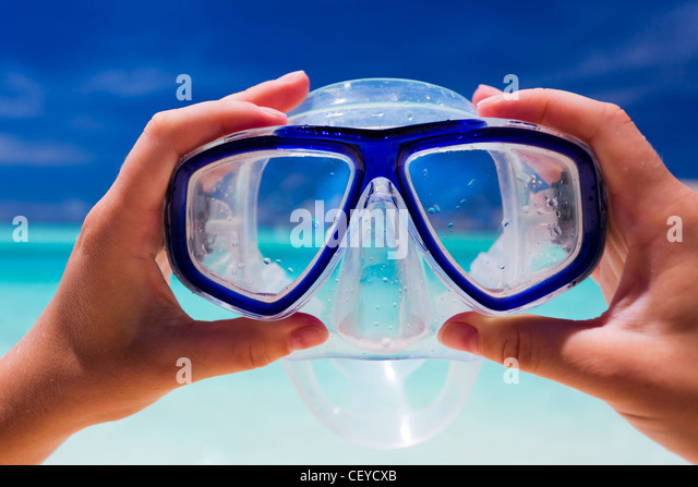 Hand holding snorkel gogles against beach and sky - Stock Image