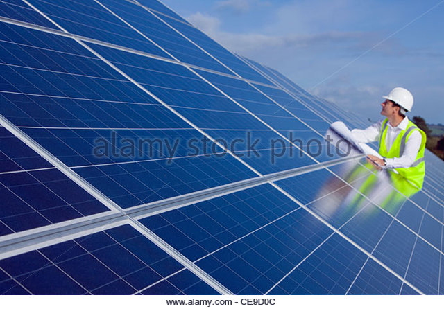 Engineer with blueprint inspecting solar panels - Stock Image