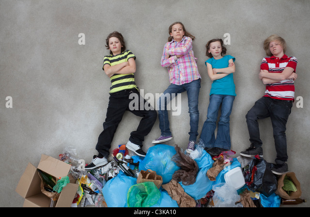 Children on stack of garbage and showing ecology symbol - Stock Image