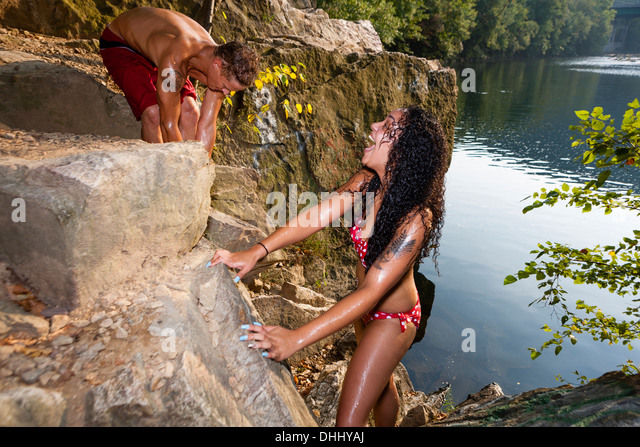 Young couple on rock ledge, Hamburg, Pennsylvania, USA - Stock-Bilder