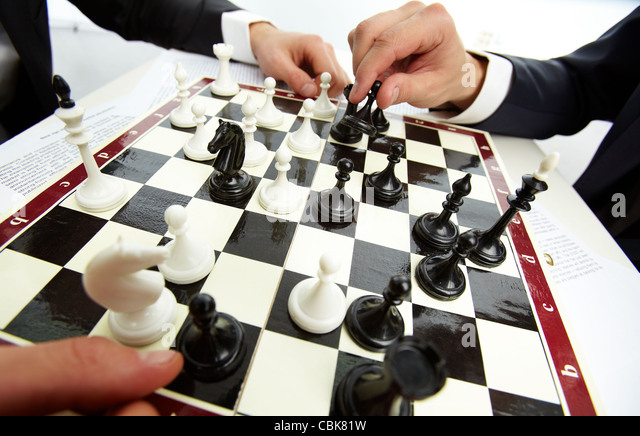 Image of human hand with chess figure making move - Stock Image