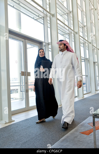 Arab businessman and businesswoman talking while walking in office hallway. - Stock Image