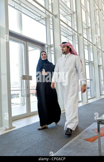 Arab businessman and businesswoman talking while walking in office hallway. - Stock-Bilder