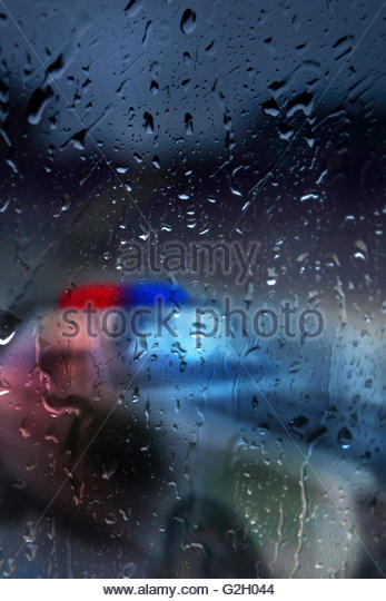 US police car behind a window with water drops on it - Stock-Bilder