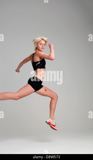 Blonde young woman in black running shorts and top, and red and white trainers, leaping and looking over her shoulder, - Stock Image