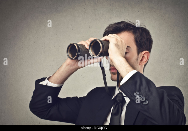 Young businessman watching through binoculars - Stock-Bilder