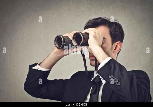 Young businessman watching through binoculars - Stock Image