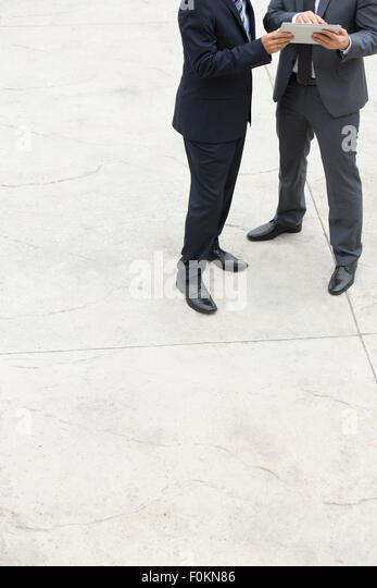Two businessmen with digital tablet standing on square - Stock Image