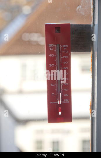 exterior thermometer on window recording centigrade and fahrenheit scales - Stock Image