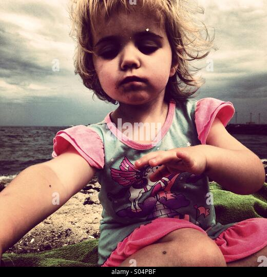 Little girl sitting on beach - Stock Image