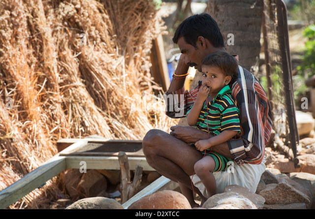 Rural Indian father and son sitting in an indian village. Andhra Pradesh, India - Stock Image