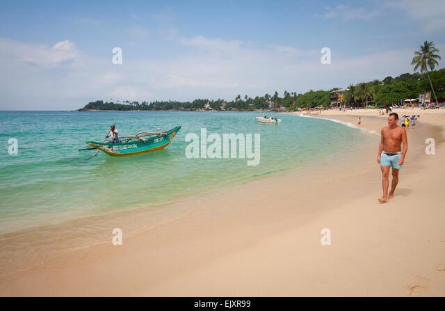 LOCAL FISHERMAN AND TOURIST WALKING ON UNAWATUNA BEACH - Stock Image