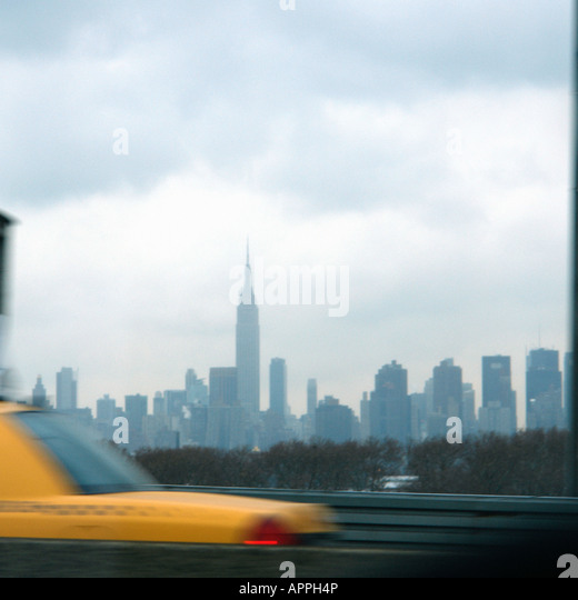 Urban Scene of a Yellow Taxi Cab and the New York City Skyline including the Empire State Building and has Copy - Stock Image