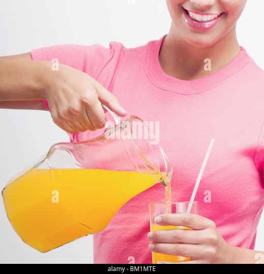 Woman pouring orange juice from a jug - Stock-Bilder
