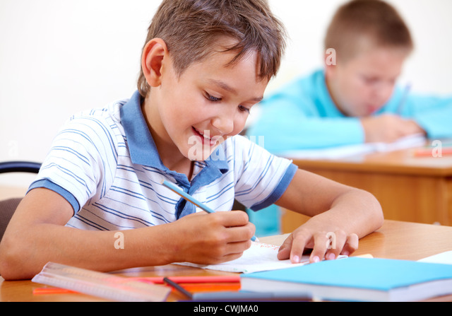 Portrait of smart lad drawing at lesson with classmates on background - Stock Image