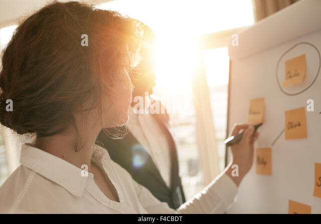 Business associates putting their ideas on flipchart during a presentation in conference room. Two business colleagues - Stock Image