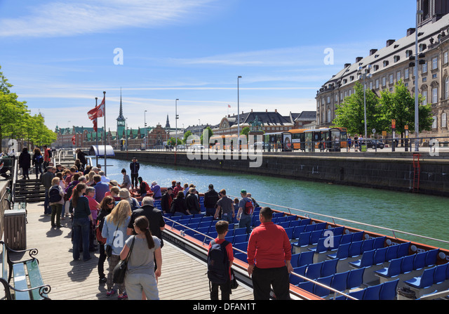 Tourists' canal cruise boat by Christiansborg Palace on Slotsholmen or Castle Isle in Copenhagen, Zealand, Denmark, - Stock Image