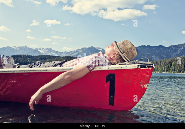 Germany, Bavaria, Mid adult man sleeping in rowing boat - Stock Image
