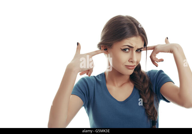 Pretty woman with disgust grimace, sticks her fingers in her ears refusing to listen to unpleasant things. - Stock Image
