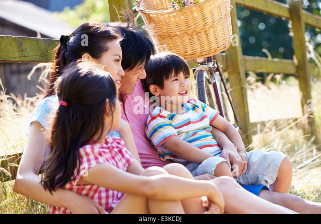 Asian Family Resting By Fence With Old Fashioned Cycle - Stock Image