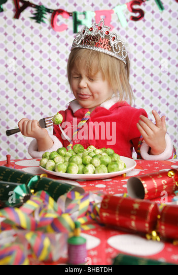 A three year old sitting at a table with Christmas decorations and a plate full of sprouts pulling a face in disgust. - Stock Image