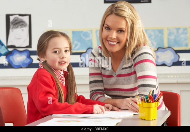 Female Primary School Pupil And Teacher Working At Desk In Classroom - Stock Image
