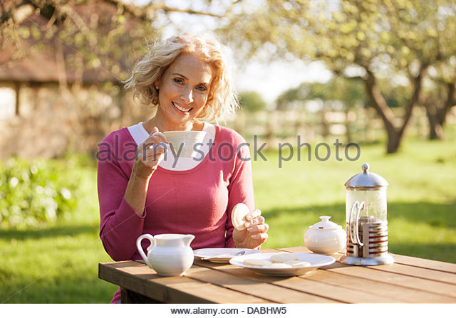 A mature woman having coffee and biscuits in a garden - Stock Image
