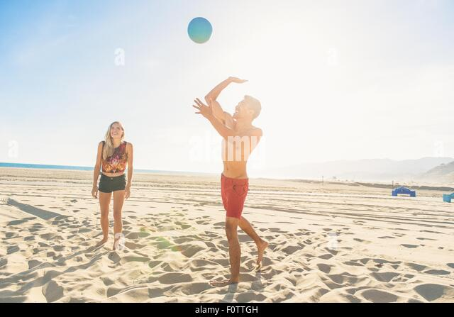 Young man on beach about to to strike volleyball - Stock Image