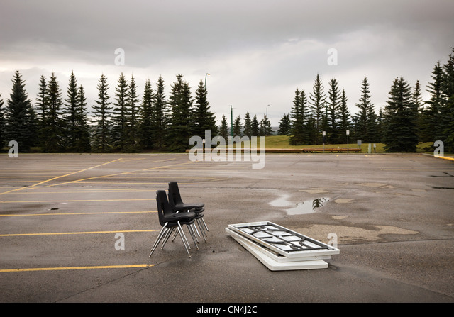 Chairs and tables left in a parking lot - Stock Image