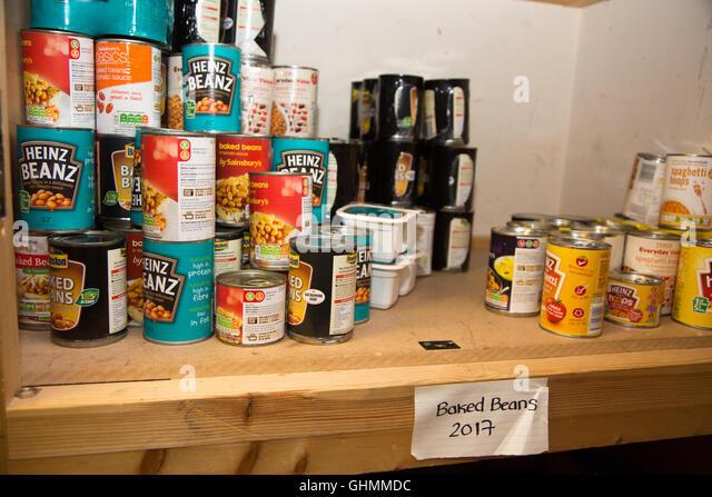 Tins of baked beans and spaghetti on a shelf at North Paddington foodbank - Stock Image