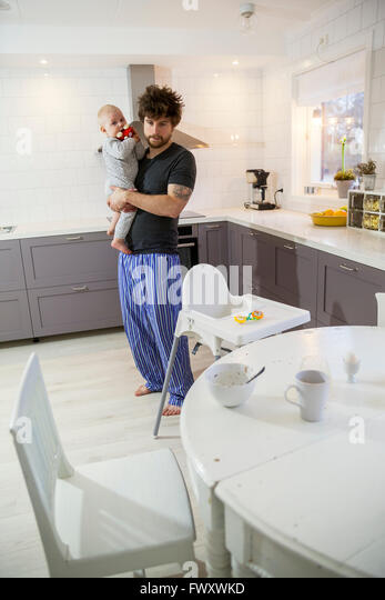 Sweden, Father holding son (12-17 months) in kitchen - Stock Image