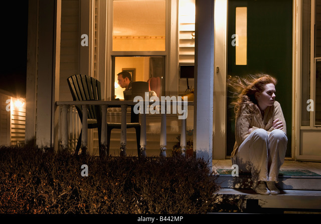 Woman sitting outside of her house - Stock Image