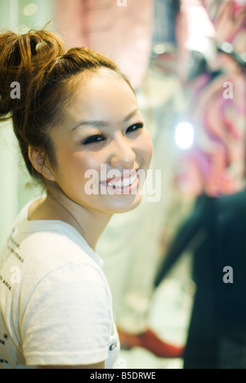 Young woman smiling over shoulder at camera, portrait - Stock Image