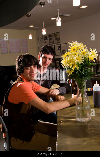 Two smiling affectionate young men in a restaurant - Stock-Bilder