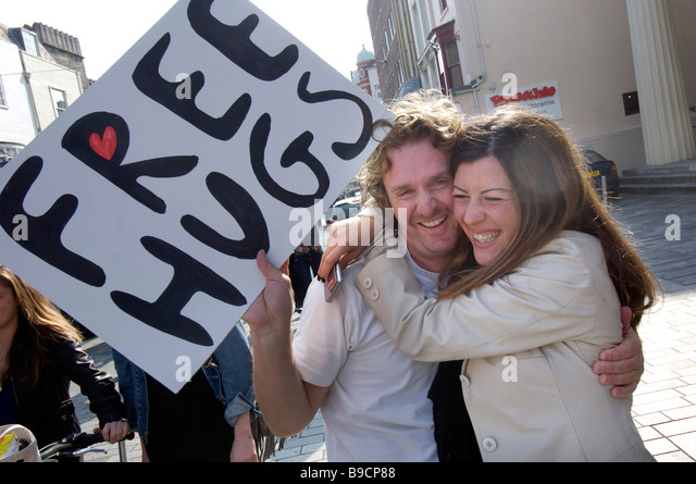 A young couple give each other a spontanious hug in central Brighton - Stock-Bilder